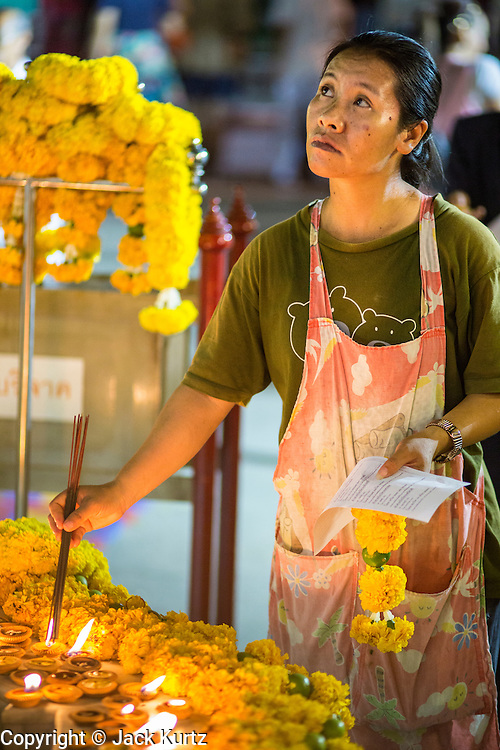 27 JANUARY 2013 - BANGKOK, THAILAND:  A woman lights incense before praying during Thaipusam at Dhevasathan (the Brahmin Shrines) on Dinso Rd in Bangkok. Thaipusam is a Hindu festival celebrated primarily by the Tamil community in South East Asia on the full moon in the Tamil month of Thai (Jan/Feb). Pusam refers to a star that is at its highest point during the festival. The festival commemorates both the birthday of the Hindu god Murugan, son of Shiva and Parvati, and the occasion when Parvati gave Murugan a vel (a lance) so he could vanquish the evil demon Soorapadman. The holy day is celebrated by Brahmins in Thailand. Brahmanism was the court religion before Buddhism came to Thailand and before the foundation of Sukhothai. Both religions are combined in the Thai way of life and its customs and ceremonies.      PHOTO BY JACK KURTZ