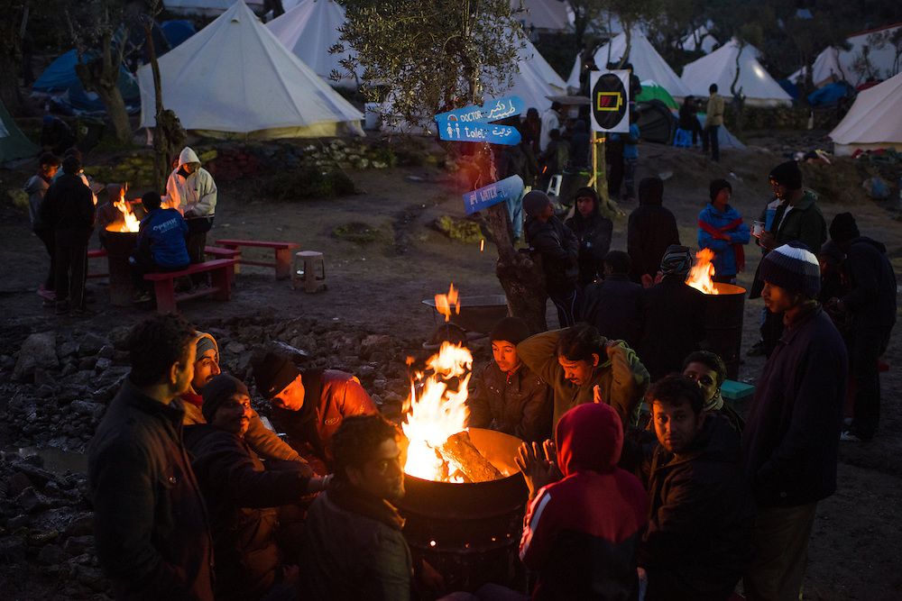 Refugees warm themselves on a fire at Better Days for Moria camp on March 19, 2016 on Lesbos Island near Moria, Greece.