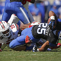 UK running back Jonathan George is brought down by U of L safety Calvin Pryor in the first half as the University of Kentucky plays the University of Louisville at Commonwealth Stadium in Lexington, Ky. Saturday Sept. 14, 2013. Photo by David Stephenson