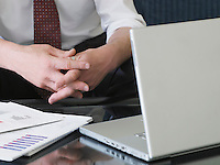 Business man using laptop sitting on sofa mid section close-up of hands