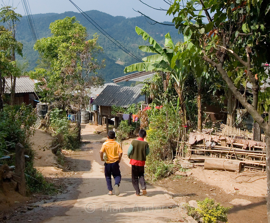 Two boys walking along a street in a typical Thai village, Ban La Up, Mae Hong Son Province, Thailand