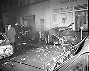Car Bomb Damage in Dublin (E10)..1972.02.12.1972..12.02.1972..2nd December 1972..On the morning of 2nd December '72 two car bombs exploded in Dublin City. At Sackville Place two busmen were killed as they waited in their car to resume work. The busmen were named as George Bradshaw (30) and Thomas Duffy (23). The bomb was thought to be planted by a Northern Ireland subversive group who hoped to influence legislation going through Dail Eireann in relation to the I.R.A...Picture shows a detective and garda taking in the scene at Sackville Place where the two busmen lost their lives. In the background, firemen are seen entering a smouldering building.
