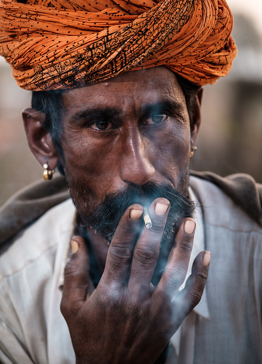 PUSHKAR, INDIA - CIRCA NOVEMBER 2018: Cameleer smoking early morning in the Pushkar Camel Fair grounds. It is one of the world's largest camel fairs. Apart from the buying and selling of livestock, it has become an important tourist destination. The city of Pushkar is a pilgrimage site for Hindus and Sikhs.