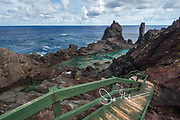 Steps lead down to St. Paul's Pool, a natural pool found along the coast of the volcanic landscape of Pitcairn island.