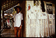 Rubber tree tapper stands in home beside posters honoring Chico Mendes; Seringal Cachoeira, Acre Brazil