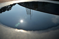 Talley Student Union tower reflected in a puddle in a seat along Stafford Commons.