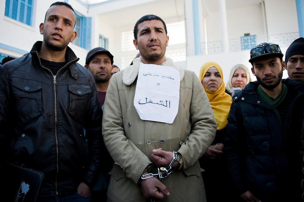 """January 2016, Kasserine, Tunisia. A man protest in front of the main entrance of the regional headquarters of the Kasserine Governate demanding development and jobs. """"The keys of my chain is employment""""."""