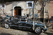 A car damaded by the earthquake abandoned in historical center city. On 6 April 2009 a strong earthquake hit the city of L'Aquila, in the central Abruzzo region of Italy, leaving 308 dead and tens of thousand homeless. 4  years after In the historical center of the city few signs of reconstructions could be seen. On the other hand the effects of the of abandonment add up to the destruction of the quake. .