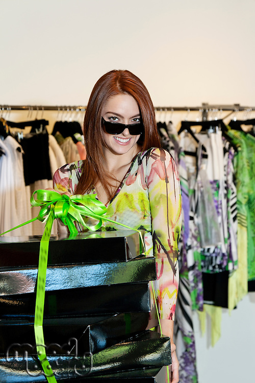 Portrait of a happy woman wearing sunglasses while carrying clothes boxes in fashion store