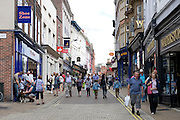 Shoppers in High Ousegate, York, UK, an historic street which is partly cobbled.