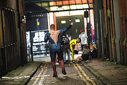 © Licensed to London News Pictures . 27/12/2015 . Wigan , UK . A man dressed as Superman pulls his costume back on after urinating in a doorway . Revellers in Wigan enjoy Boxing Day drinks and clubbing in Wigan Wallgate . In recent years a tradition has been established in which put on fancy dress for a Boxing Day night out . Photo credit : Joel Goodman/LNP