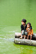 Two children on the lake in the H'Mong village in Pho Cao, Ha Giang. Their life are so hard, depending on nature and weather a lot. All their hands and feet are so dirty. They play all day with soil, water, and the older takes care the younger. Their parent, sister and brothers are on the farm until sun dawn. They love candy so much, if you have a chance to visit there, remember to bring a lot of candy for them.