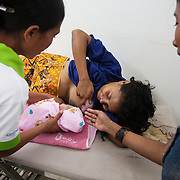 Gelina is 15 min old and it's her first time to latch on to her mother's breast to feed. Health worker Santina help the mother, Gintown Rodrigues, and baby to connect and there are no problems, Gelina happily drinks away.the Infant mortality rates are very high in Timor-Leste and one of the reasons for that is poor nutrition. Alola advocate breast feeding till at least two years old and teach women about nutritious supplements such as boiled and mashed rice w vegetables and eggs.  Fundasaun Alola is a not for profit non government organization operating in Timor Leste to improve the lives of women and children. Founded in 2001 by the then First Lady, Ms Kirsty Sword Gusmao, the organization seeks to nurture women leaders and advocate for the rights of women.