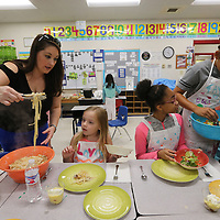 Rachel Davis, left, and Taylor Norwood, 10, right, begin to serve up lunch to Laya Smith, 8, and Jordyn Akins, 12, at this week's cooking camp.