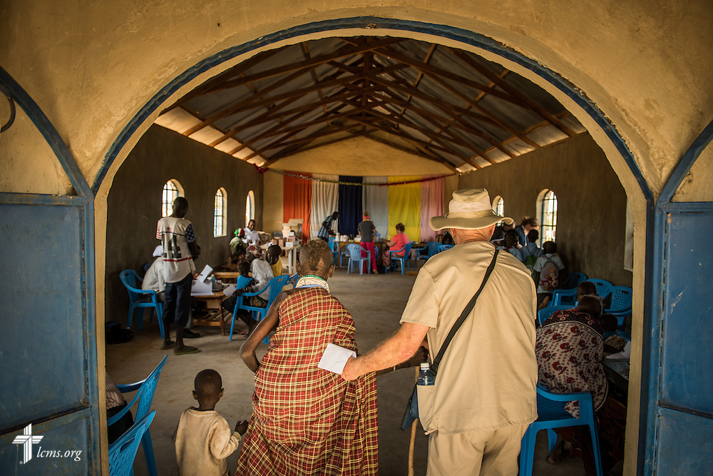 Brian Lund, a member of Faith Lutheran Church, Merritt Island, Fla., escorts an elderly patient to the pharmacy during the LCMS Mercy Medical Team on Monday, June 20, 2016, in Nataparkakono, a village in Turkana, Kenya.  LCMS Communications/Erik M. Lunsford