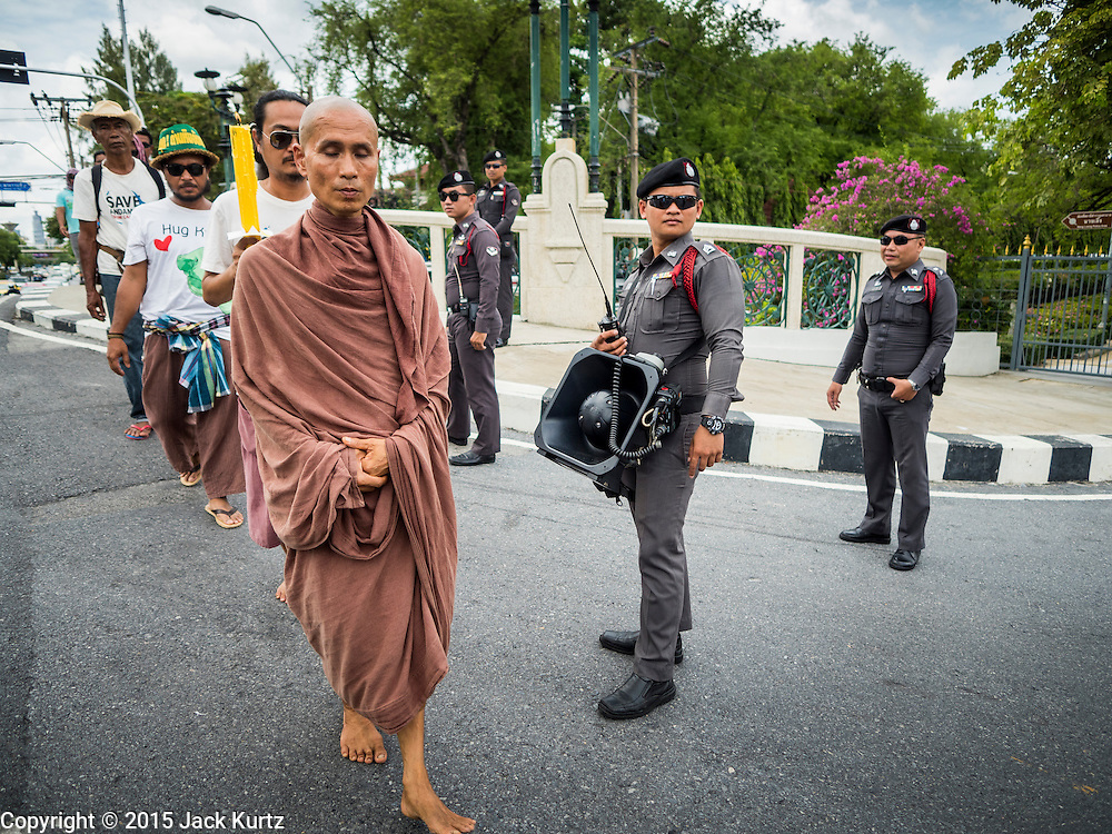 22 JULY 2015 - BANGKOK, THAILAND:  DADODIN PATAVATTO, a Buddhist monk, leads a silent march past Thai police officers guarding Government House, which is the office of the Prime Minister in Bangkok. More than 100 people from Krabi province, members of the Save Andaman from Coal Network (SACN) have staged a series of marches and sit-ins outside the Prime Minister's office. They are opposed to plans to build an 800 megawatt coal fired power plant near southern Thailand's Andaman coast about 650 kilometers (400 miles) south of Bangkok. The area is famous for its pristine beaches. Residents worry that the coal fired power plant will pollute the area and send power to Bangkok.   PHOTO BY JACK KURTZ