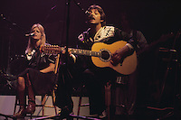 Paul McCartney and his wife Linda McCartney (1941 - 1998) on stage with Wings at London's Empire Pool, October 1976.