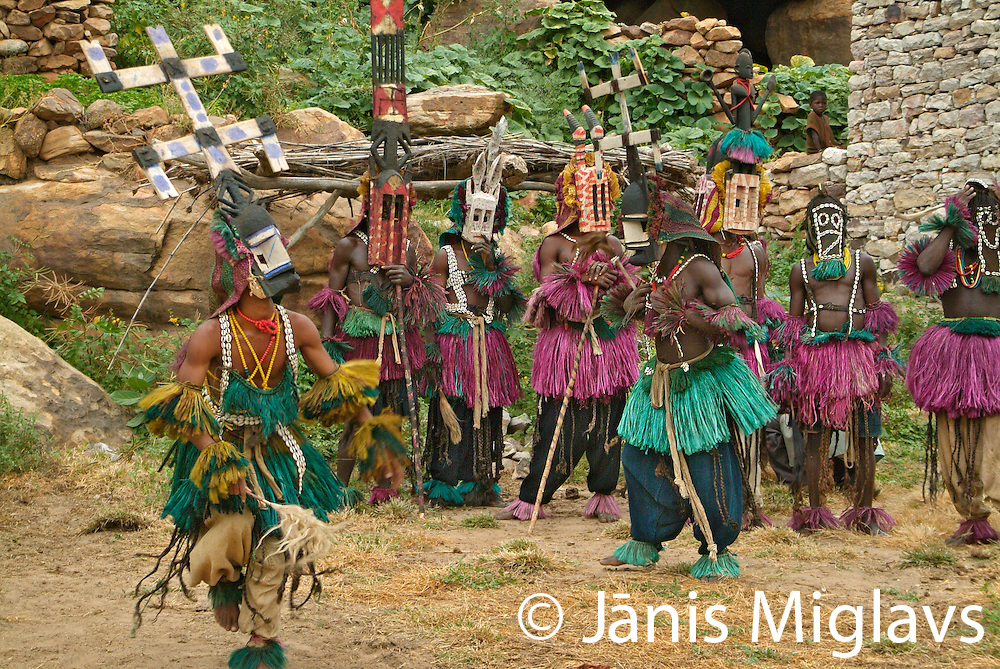 Dogon men wearing  traditional colored grass clothes and wooden masks perform a traditional mask dance in the village of Kondou in Dogon country, Mali, West Africa.