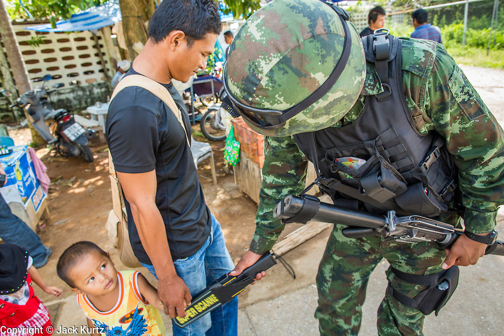 """25 OCTOBER 2012 - TAK BAI, NARATHIWAT, THAILAND: A Muslim boy watches a Thai soldier search his father in Tak Bai, Thailand. The """"Tak Bai Incident"""" took place on Oct. 25 in Tak Bai, Narathiwat, Thailand during the Muslim insurgency in southern Thailand. On that day, a crowd gathered to protest the arrest of local residents. Police made hundreds of arrests during the protest and transported the arrested to Pattani, about two hours away, in another province. They were transported in locked trucks and more than 80 people suffocated en route. This enraged local Muslims and shocked people across Thailand. No one in the Thai army accepted responsibility for the deaths and no one was ever charged. In the past, the anniversary of the incident was marked by protests and bombings. This year it was quiet. More than 5,000 people have been killed and over 9,000 hurt in more than 11,000 incidents, or about 3.5 a day, in Thailand's three southernmost provinces and four districts of Songkhla since the insurgent violence erupted in January 2004, according to Deep South Watch, an independent research organization that monitors violence in Thailand's deep south region that borders Malaysia.   PHOTO BY JACK KURTZ"""