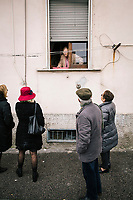"""NAPLES, ITALY - 2 FEBRUARY 2019: Passengers of the literary bus tour """"Neapolitan Novels"""" chat with an elderly woman living in the Rione Luzzatti, the neighborhood in which Elena Ferrante's """"My Brilliant Friend"""" is set, in Naples, Italy, on February 2nd 2019.<br /> <br /> In December 2018, City Sightseeing - the world's largest sightseeing tour bus operator - inaugurated the """"Brilliant Naples"""" tour, inspired by the locations in """"Neapolitan Novels"""", a 4-part series by the Italian novelist Elena Ferrante. The series has sold over 10 million copies in 40 countries. The first book in the series has also been adapted into an HBO television series entitled, """"My Brilliant Friend."""""""