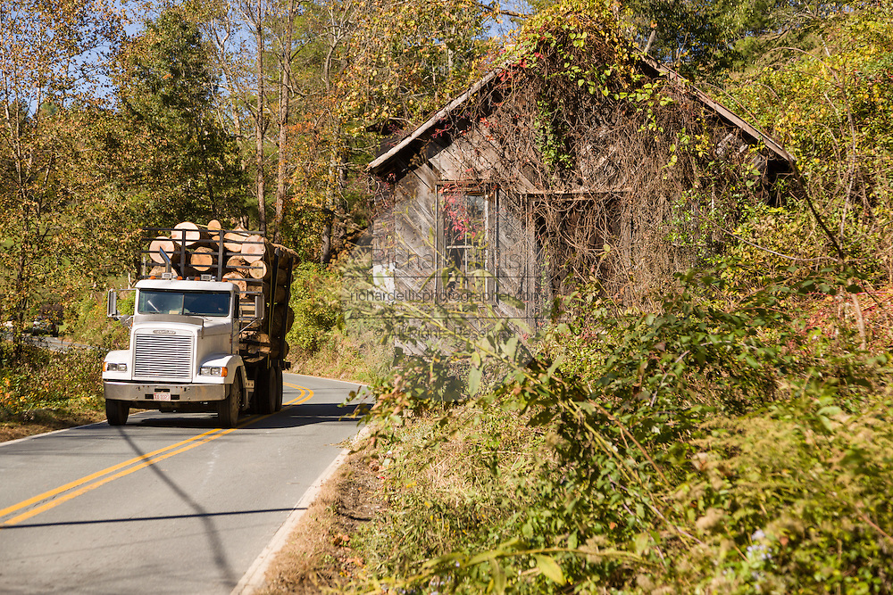 A logging truck passes an old wooden barn on a rural road in Prices Creek, North Carolina.