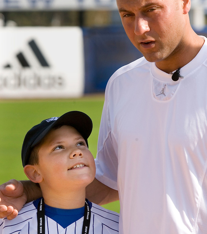 "Jordan Boone, 10, of Las Vegas, Nevada glances up towards New York Yankee's Derek Jeter while posing for a photo during the Upper Deck, ""Play Ball! with Derek Jeter"" clinic on Saturday, February 10, 2007 at Legends Field in Tampa, Florida.  Justin Topa, 15, of Binghampton, New York, Jordan Boone, 10, of Las Vegas, Nevada, Bryce Porter, 10, of Costa Mesa, California and Gavin Leonard, 9, of Bristol, Virginia, each won the grand prize to meet Jeter through various promotions on www.UpperDeckKids.com in 2006. UPPER DECK/Scott Audette"