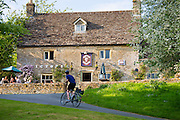 Cyclists cycling past drinkers sitting outside typical English pub The Victoria in the village of Eastleach Martin, The Cotswolds, UK