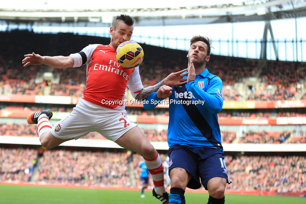 11 January 2015 - Barclays Premier League - Arsenal v Stoke City - Mathieu Debuchy of Arsenal collides with Marko Arnautovic of Stoke City before hitting the advertising boards - Photo: Marc Atkins / Offside.