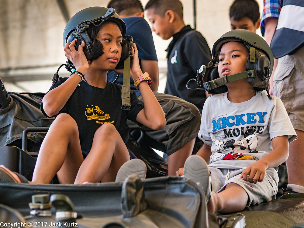 """14 JANUARY 2017 - BANGKOK, THAILAND: Children wearing tanker's helmet sit on top of a Royal Thai Army M60 A3 Main Battle Tank during Children's Day activities at the King's Guard, 2nd Cavalry Division base in Bangkok. Thailand National Children's Day is celebrated on the second Saturday in January. Known as """"Wan Dek"""" in Thailand, Children's Day is celebrated to give children the opportunity to have fun and to create awareness about their significant role towards the development of the country. Many government offices open to tours and military bases hold special children's day events. It was established as a holiday in 1955.       PHOTO BY JACK KURTZ"""