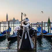 VENICE, ITALY - FEBRUARY 25:  A woman dressed in Carnival Costume poses in front of gondolas in Saint Mark's Square  on February 25, 2014 in Venice, Italy. The 2014 Carnival of Venice will run from February 15 to March 4 and includes a program of gala dinners, parades, dances, masked balls and music events.  (Photo by Marco Secchi/Getty Images)