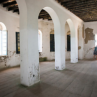 Two Western female tourists look out of a window from an empty room in the former officers quarters of the Cape Coast Castle, a UNESCO World Heritage Site located along the Gold Coast of Ghana.