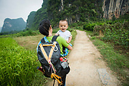 A smiling baby boy looking over his mothers shoulder as she walks down a dirt road near Yangshuo, China (Model Released, Rachel and Tintin Ouyang).