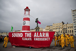 "© Licensed to London News Pictures . 22/09/2019. Brighton, UK. The words "" Sound the alarm climate emergency "" written on the side of the lighthouse boat . Environmental campaigners from Extinction Rebellion highlight the climate emergency and deploy a large red and white lighthouse lightship named "" Greta "" , on Brighton Promenade , during the second day of the 2019 Labour Party Conference from the Brighton Centre . Photo credit: Joel Goodman/LNP"