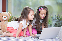 Cute little sisters using laptop on bed at home