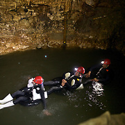 Participants  on black water tubing while Black Water rafting in the Waitomo Glowworm Caves, Waitomo, North Island, New Zealand..The Legendary Black Water Rafting Company is New Zealand's first black water adventure tour operator which takes tourists through the  Ruakuri Cave at Waitomo..The five hour expedition combines abseiling the 35 metre entrance. climbing, a flying fox. black water tubing, leaping and floating through Ruakuri Cave and observing glow worms. The journey concludes  into the sunlight of the Waitomo forest..Waitomo, New Zealand, 14th December  2010 Photo Tim Clayton