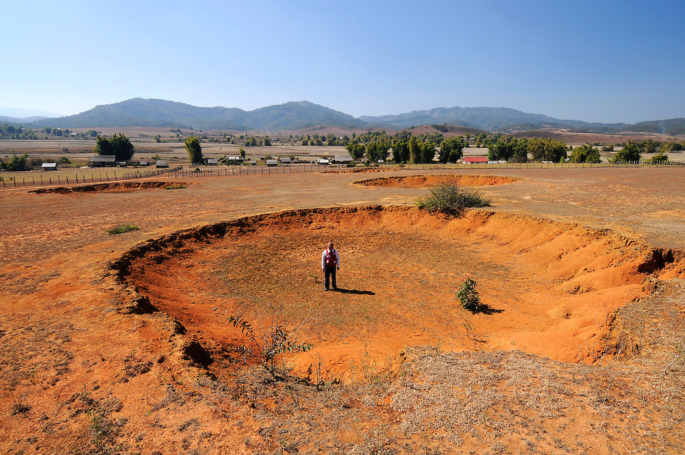 A man in a field of bomb craters in Ban Kay, Laos.  Much of Laos looks like a pastoral moonscape.  30 years later nothing grows these craters, which are a prime source of bomb fragment for scrap metal hunters.  2,000 - 3,000 lb fragmentation bombs are said to have created these craters.  The US dropped approximately 2 million tons of bombs on Laos making it one of the most heavily bombed countries in world history.