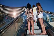 "Women in short skirts ride an outdoor escalator on the Las Vegas 'Strip."""
