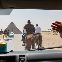 Egypt, Cairo, View through windshield of taxi following tourists' horses approaching Pyramids in Giza