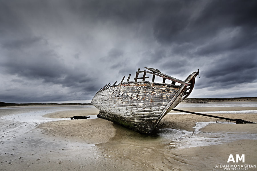 Ship Wreck Bunbeg<br /> County Donegal<br /> by Aidan Monaghan<br /> The wrecked &lsquo;Cara Na Mara&rsquo; (Friend of the Sea) on the tidal sandbanks of the Magheraclogher Beach County Donegal. Known to the locals as &lsquo;B&aacute;d Eddie&rsquo; (Eddie&rsquo;s Boat) the ship ran aground in the early 1970&rsquo;s due to severe weather conditions at sea. Today the carcass of a hull has taken on an organic  quality, seething with colour and texture as thousands of crustacea cling to and are embedded within  its timbers. <br /> <br /> The daily high tide at Bunbeg  continues to reach the wreck, but this is not enough to free it from the sandbank upon which it is held prisoner. Only  the slow but relentless passing of time aided by the processes of decay, will eventually return the &lsquo;Cara Na Mara&rsquo; to the sea.<br /> <br /> Malin Head County Donegal