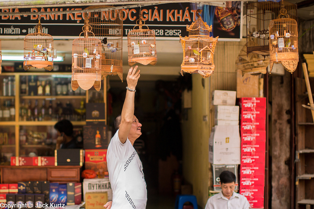 02 APRIL 2012 - HANOI, VIETNAM: A man tends to his pet birds on street in Hanoi, the capital of Vietnam.    PHOTO BY JACK KURTZ