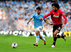 Manchester City's Sergio Aguero jostles for the ball with Manchester United's Marouane Fellaini - Photo mandatory by-line: Dougie Allward/JMP - Tel: Mobile: 07966 386802 22/09/2013 - SPORT - FOOTBALL - City of Manchester Stadium - Manchester - Manchester City V Manchester United - Barclays Premier League