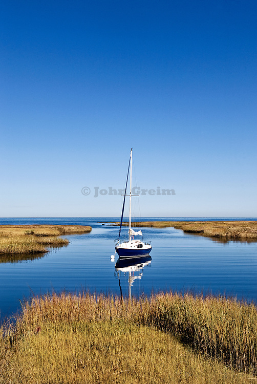Sailboat anchored in a salt marsh leading into Cape Cod Bay, Cape Cod, Massachusetts, USA