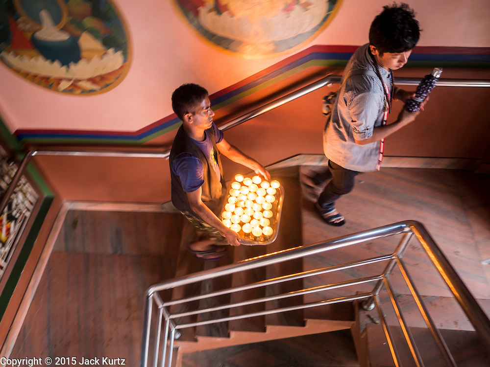 31 JULY 2015 - KATHMANDU, NEPAL:  A man brings butter lamps to the top of floor of a Tibetan monastery for the full moon procession around Bodhnath Stupa. Bodhnath Stupa in the Bouda section of Kathmandu is one of the most revered and oldest Buddhist stupas in Nepal. The area has emerged as the center of the Tibetan refugee community in Kathmandu. On full moon nights thousands of Nepali and Tibetan Buddhists come to the stupa and participate in processions around the stupa. The stupa was heavily damaged in the earthquake of 25 April 2015 and people are no longer allowed to climb on the stupa, now they walk around the base and pray with butter lamps.  PHOTO BY JACK KURTZ