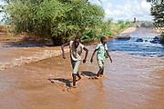 Turkana village children wade through knee-high water on a road inundated by unseasonal heavy rain.