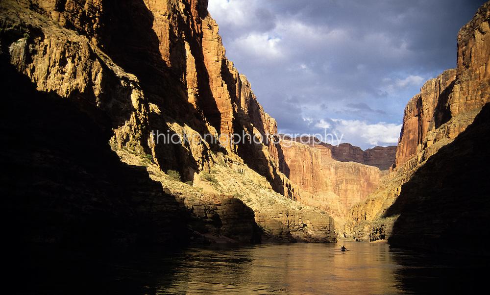 Lone kayaker is dwarfed by dramatically lit canyon walls of the Grand Canyon, Arizona