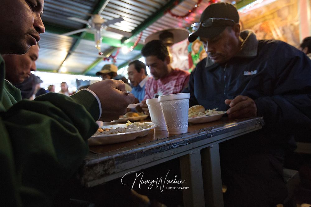 "Men sit down to a meal at the ""comedor,"" the kitchen and dining hall of the Aid Center for Deported Migrants in Nogales, Mexico, Dec. 20. The center is a project of the Kino Border Initiative, a bi-national church ministry to migrants.  (CNS photo/Nancy Wiechec)"