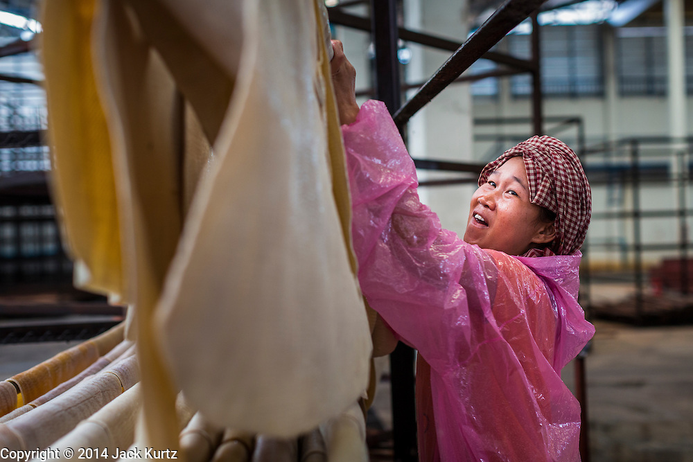 02 SEPTEMBER 2014 - BO THONG, CHONBURI, THAILAND: A worker at Bothong Rubber Fund Cooperative in Bo Thong, Chonburi, Thailand, hangs rubber sheets before putting them in a large smoker to dry after the sheets were washed. Thailand is the leading rubber exporter in the world. In the last two years, the price paid to rubber farmers has plunged from approximately 190 Baht per kilo (about $6.10 US) to 52 Baht per kilo (about $1.60 US). It costs about 65 Baht per kilo to produce rubber ($2.05 US). A rubber farmer in southern Thailand committed suicide over the weekend, allegedly because the low prices meant he couldn't provide for his family. Other rubber farmers have taken jobs in the construction trade or in Bangkok to provide for their families during the slump.    PHOTO BY JACK KURTZ