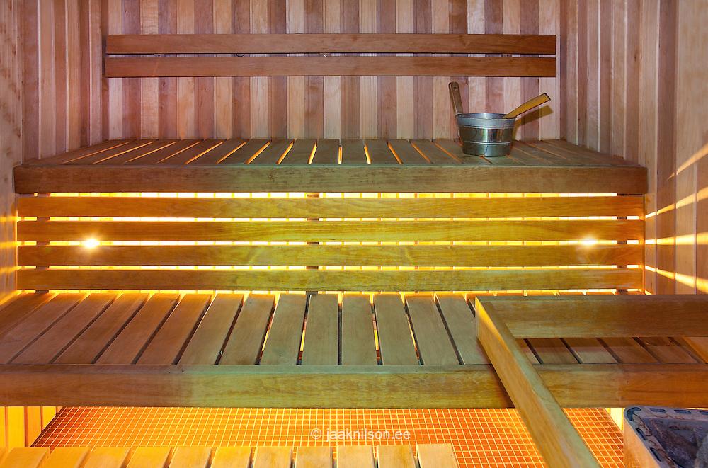 Sauna room in Viimsi Spa Hotel in Tallinn, Estonia. Wooden bench and metal pitcher of water.