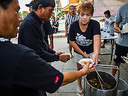 05 NOVEMBER 2016 - BANGKOK, THAILAND: Members of the Pom Mahakan community, near the Grand Palace, serve soup to mourners walking down to the palace to honor the King. Thais are honoring their late King, Bhumibol Adulyadej, also known as Rama IX, in various ways. Many barbers are offering mourners free haircuts on the streets near the Grand Palace, where the King is lying in state and communities around the palace are offering free meals to mourners walking to the palace.     PHOTO BY JACK KURTZ