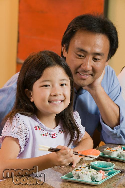 Father Watching Daughter Eat Sushi